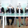 Row of business executives with smiley faces in front of their faces